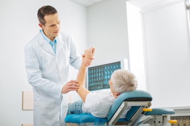 Examen profesional. terapeuta habilidoso alegre positivo de pie en su oficina y comprobando la salud del paciente mientras hace su trabajo