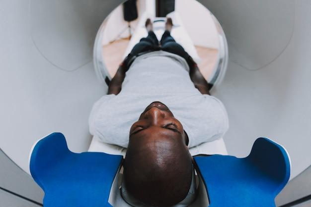 Examen de tc para hombre afro en clínica de neurología.