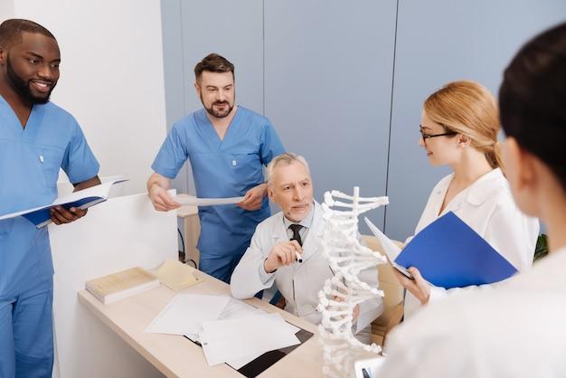 Examen en la universidad médica. mentor calificado optimista interesado que trabaja y tiene la clase en la facultad de medicina mientras toma el examen