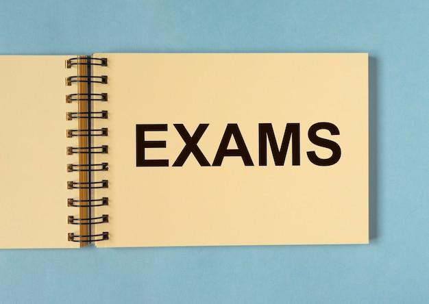 Exámenes de palabras en papel de cuaderno sobre fondo azul.