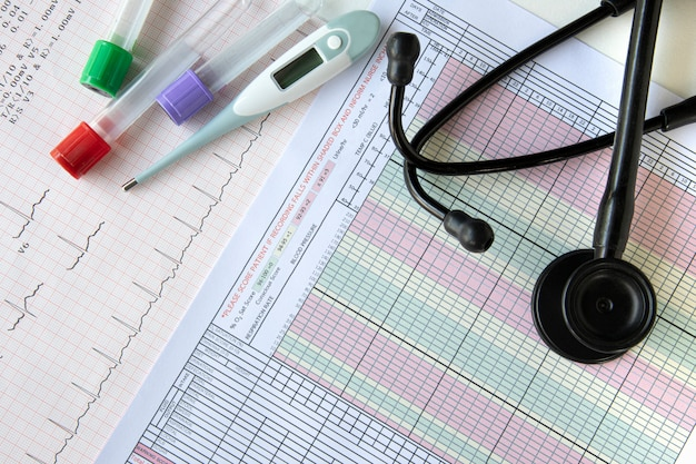 Exámenes de sangre, un termómetro digital y un estetoscopio sobre una mesa