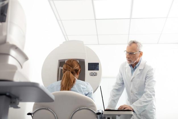 Examinar a la mujer atentamente. especialista en ojos canosos con gafas examinando atentamente a la mujer