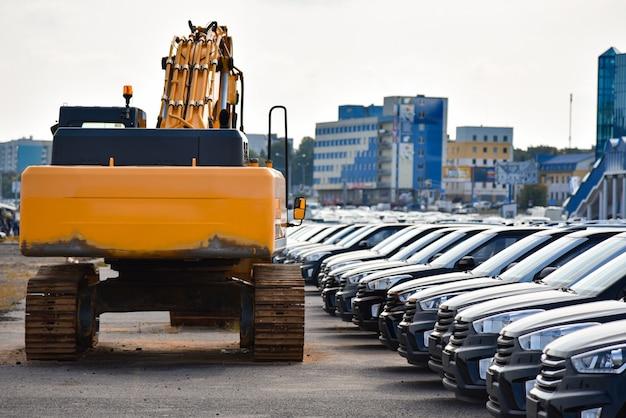 Excavadora amarilla cerca de una fila de autos rojos nuevos en la calle