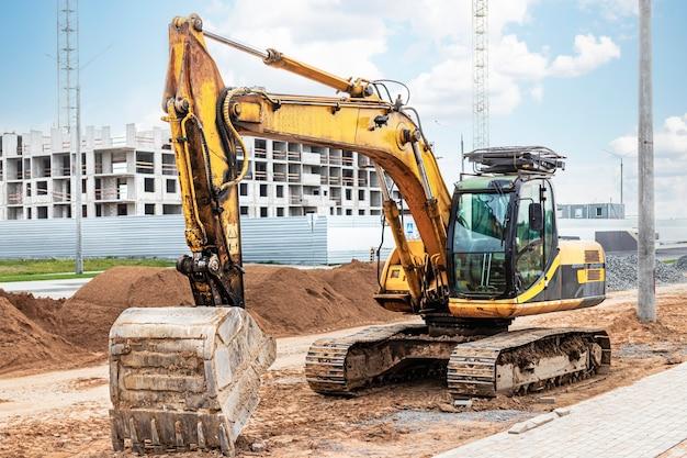 Excavadora de cadenas pesada con un gran cucharón en el fondo del cielo del atardecer. equipo pesado de construcción para movimiento de tierras. mejora del territorio.