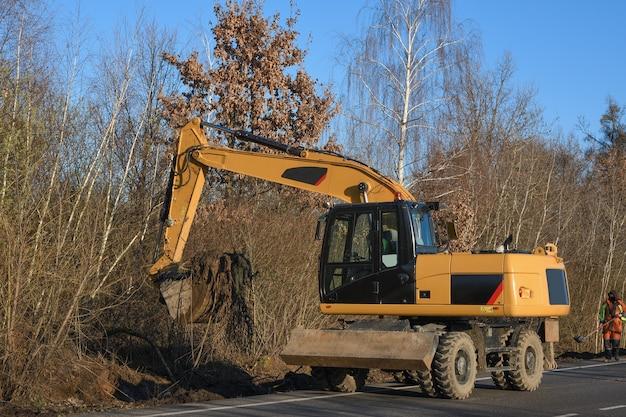 Una excavadora de cangilones despeja el borde de la carretera. obras viales. trazando un nuevo camino. cargando arcilla de excavadora y piedras