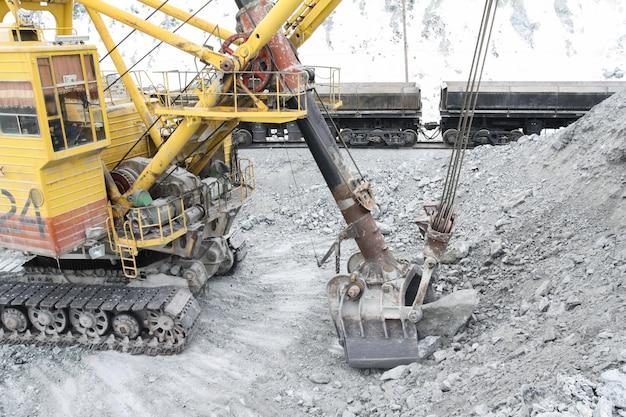 La excavadora carga las piedras en los autos.