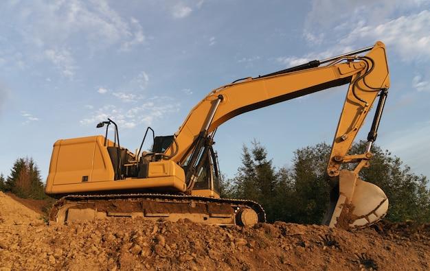 Excavadora cavando en el suelo en el sitio de construcción