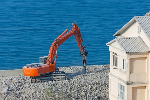 Excavadora con cizalla hidráulica contra un edificio demolido. desmantelamiento de construcción de emergencia a la orilla del mar.