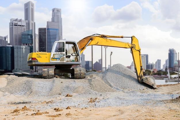 Excavadora estacionada en el montículo de la ciudad con fondo de rascacielos.