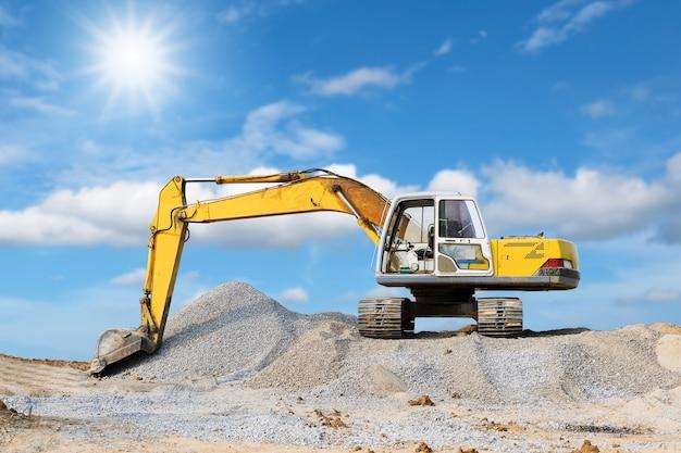 Excavadora estacionada en el montículo con luz solar y fondo de cielo azul.