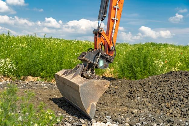 La excavadora extiende el suelo en el campo.