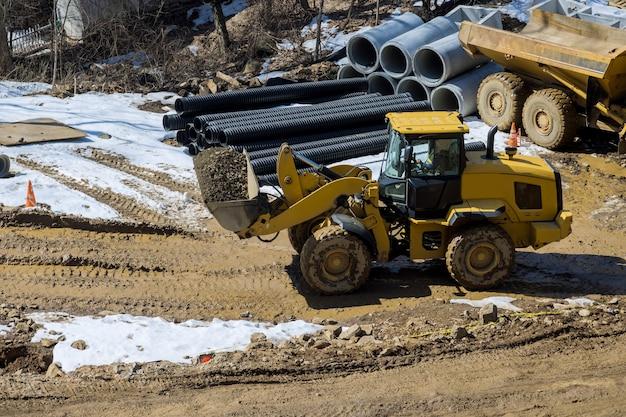 Excavadora pesada que excava el suelo que trabaja durante las obras viales, mueve la grava durante la construcción