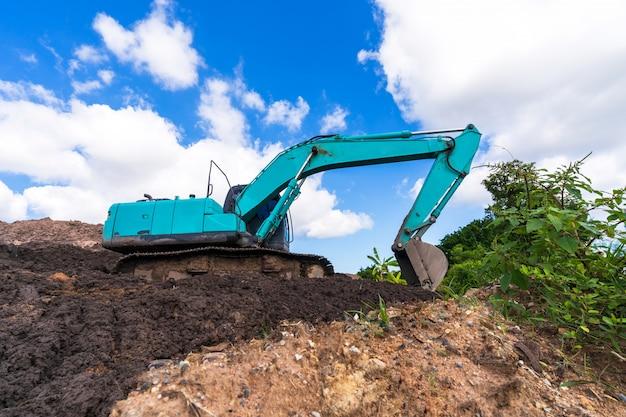 Excavadora en sitio de construcción bajo cielo azul