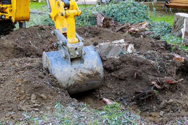 Excavadora de trabajo de jardín limpiando la tierra de árboles viejos, raíces y ramas con maquinaria de retroexcavadora en un vecindario urbano.