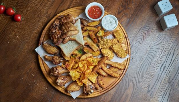 Un excelente aperitivo de cerveza es un conjunto de nuggets de pollo, papas fritas con salsa de pergamino en una bandeja de piedra. comida de pub. de cerca.