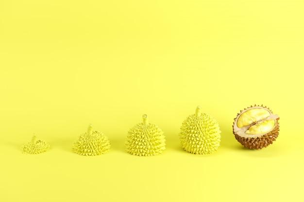 Excelente corte fresco, durian maduro y rodajas de durian pintadas en amarillo sobre fondo amarillo