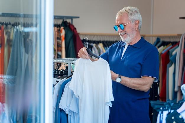 Excelente estilo. cintura para arriba del hombre de moda de pelo gris con gafas de sol eligiendo un nuevo atuendo en la tienda de ropa mientras expresa deleite en su rostro