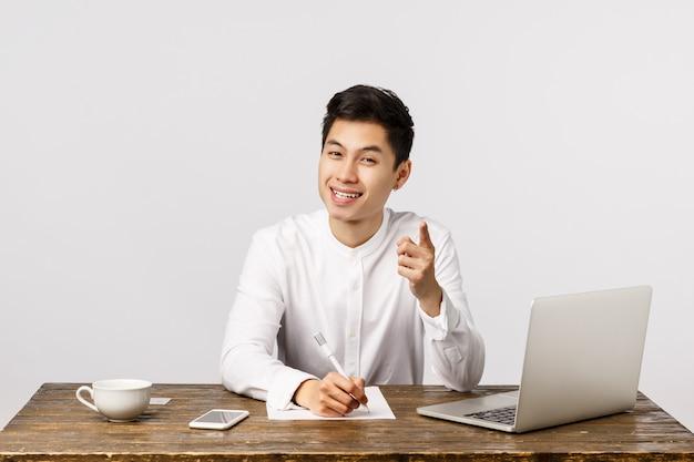 Excelente idea, escríbela. apuesto joven empresario asiático diciendo que tiene punto, señalando y tomando notas, sonriendo complacido, escuchó una idea interesante, sentado en el escritorio de oficina con computadora portátil