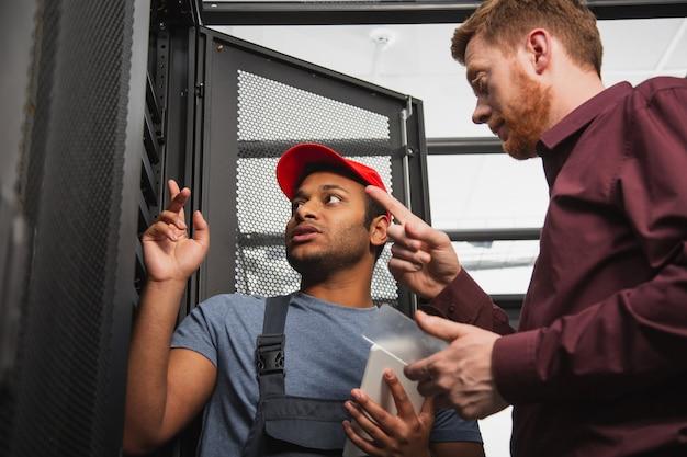 Excelentes especialistas. ángulo bajo de dos colegas inquietos que se quedan cerca del armario del servidor y hablan