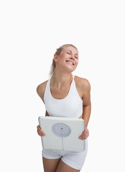 Excitada joven mujer feliz sosteniendo balanzas