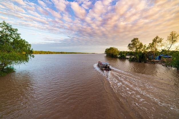 Excursión en barco en la región del delta del río mekong, ben tre, vietnam del sur. barco de madera en crucero en el canal de agua a través de la plantación de cocoteros.