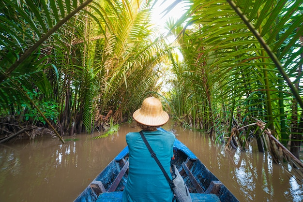 Excursión en barco en la región del delta del río mekong, ben tre, vietnam del sur. turista con sombrero vietnamita en crucero en los canales de agua a través de la plantación de cocoteros.