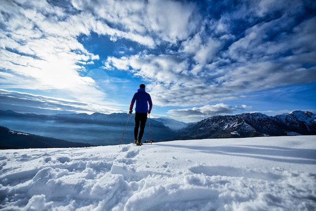 Excursión en solitario con raquetas de nieve en un día oscuro y soleado