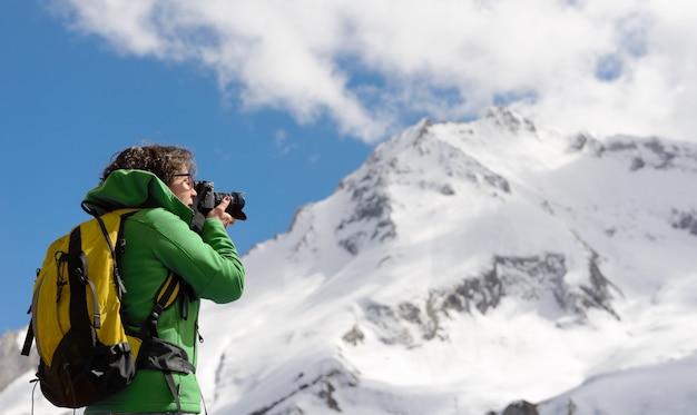 Excursionista con cámara y mochila tomando foto de hermosa montaña