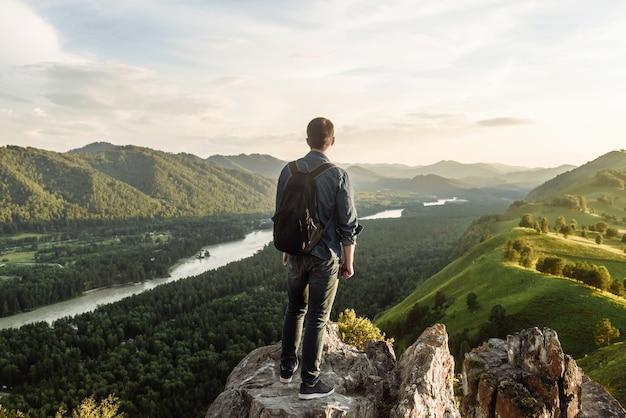 El excursionista en la cima de la montaña mira y disfruta de la vista del valle y el río en la naturaleza.