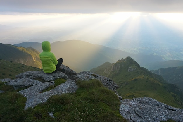 Excursionista femenina disfrutando de la vista desde la cumbre con los rayos del sol en el horizonte