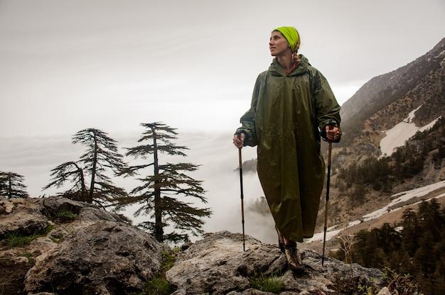 Excursionista femenina en impermeable se encuentra en la montaña