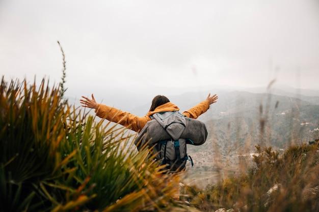 Una excursionista femenina con mochila extendiendo sus brazos en las montañas