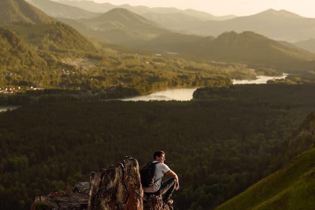 Excursionista hombre con mochila disfrutando de la vista del valle desde la cima de la montaña