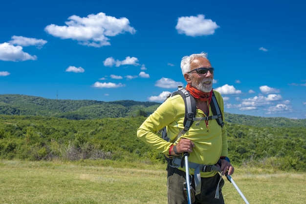 Excursionista macho de pie y sonriendo en una pradera de montaña