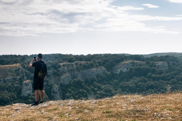 Excursionista macho tomando una foto de colinas cubiertas de vegetación con su teléfono bajo un cielo nublado