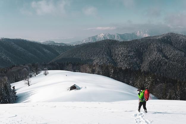Excursionista macho tomando fotos de una montaña alpina de invierno y una cabaña cubierta de nieve debajo