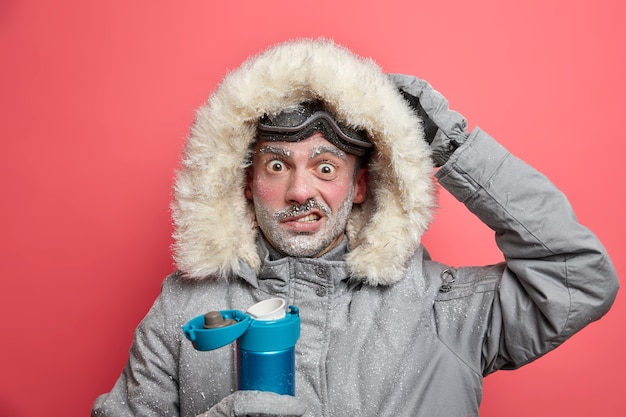 El excursionista masculino desconcertado tiene la cara congelada conmocionado por las condiciones frías en la expedición usa una chaqueta abrigada y gafas de esquí y bebe una bebida caliente.