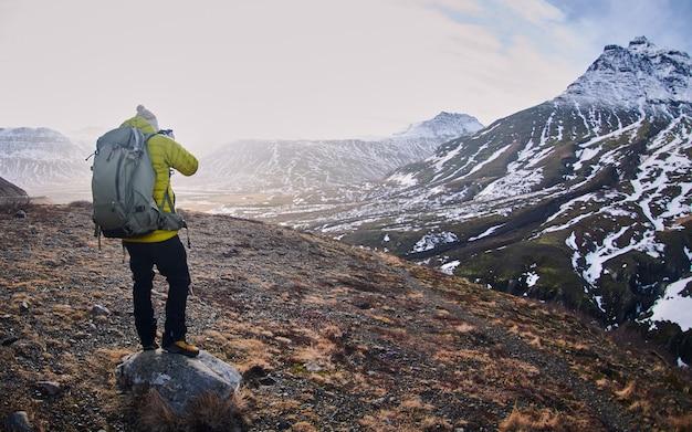 Excursionista masculino con una mochila tomando una fotografía de las montañas rocosas cubiertas de nieve.