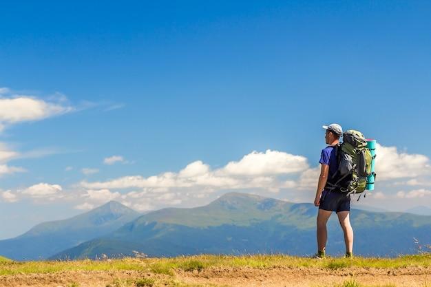 Excursionista con mochila disfrutando de la vista de la cima de una montaña hoverla en montañas de los cárpatos, ucrania