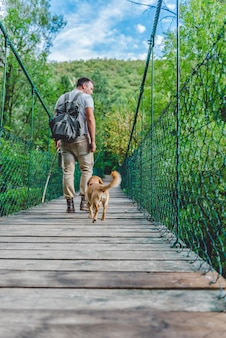 Excursionista con perro caminando sobre puente colgante de madera