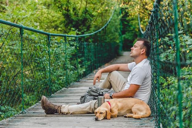 Excursionista con perro descansando sobre puente colgante de madera