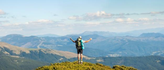 Excursionista de pie en la cima de la montaña. unidad con el concepto de naturaleza.