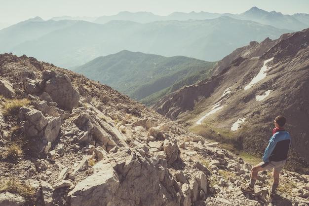 Excursionista de pie en el sendero de montaña rocosa
