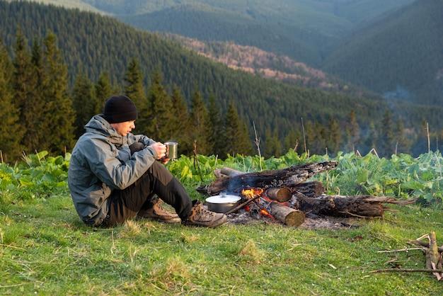 Excursionista prepara comida en una estaca en una caminata en las montañas en altitud