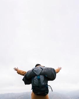 Un excursionista con su mochila estirándose las manos en la cima de la montaña