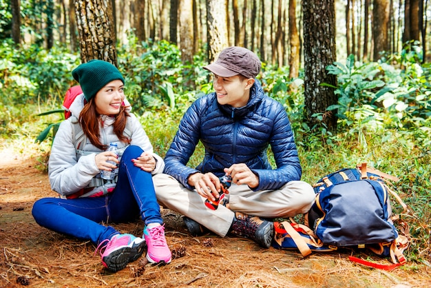 Los excursionistas asiáticos sonrientes de la pareja toman un descanso mientras que beben un agua