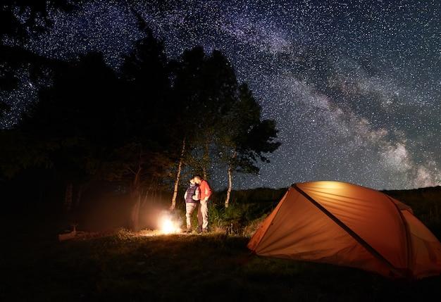 Excursionistas cerca de la fogata y la carpa en el campamento nocturno.