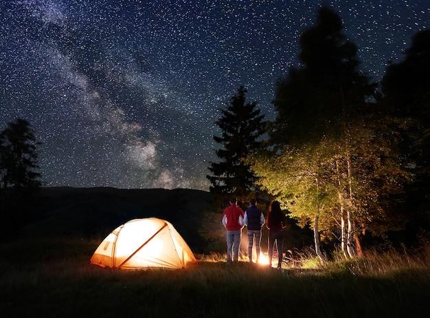 Excursionistas cerca de fogata y carpa turística en la noche.