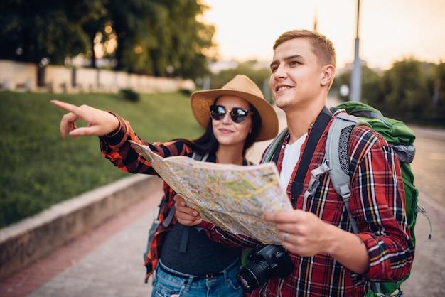 Excursionistas con mochilas que buscan atracciones de la ciudad en el mapa, excursión en ciudad turística. senderismo de verano. caminata aventura de hombre y mujer joven.