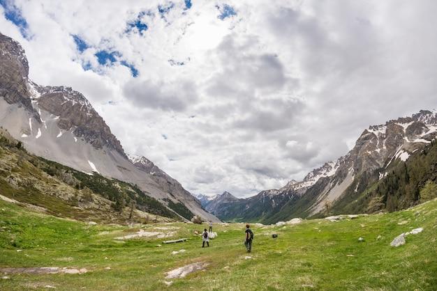 Excursionistas subiendo cuesta arriba. aventuras de verano y exploración en los alpes.
